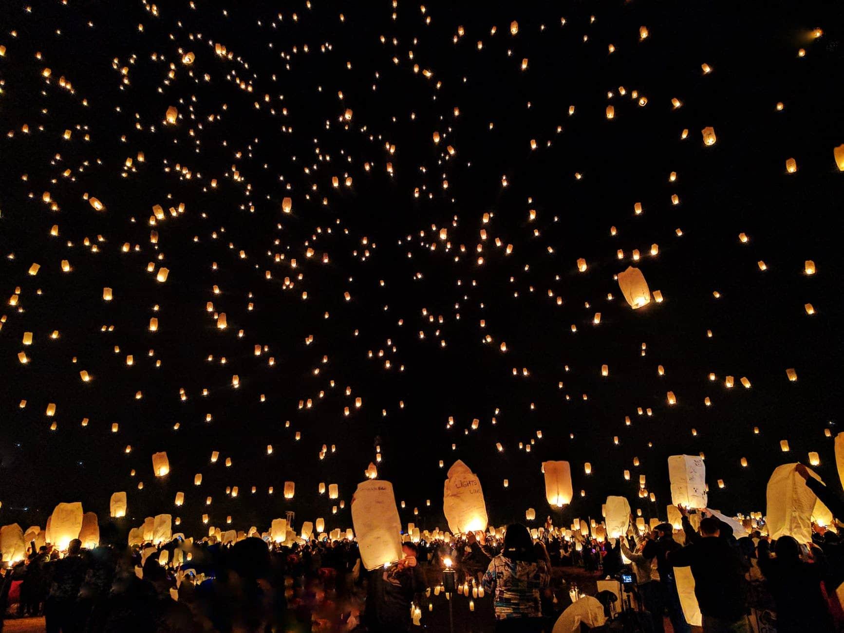 Céu noturno iluminado com pequenos balões brancos, cada um com uma vela acesa dentro.