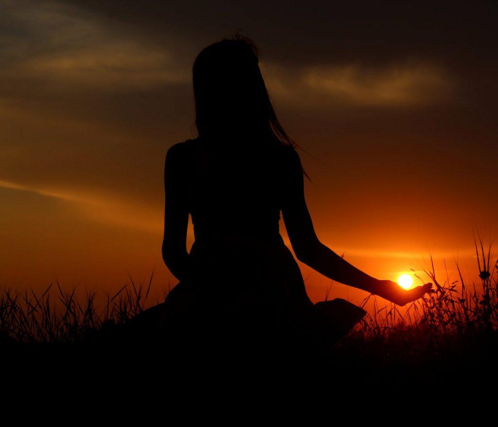 Silhueta de uma mulher em posição de meditação.