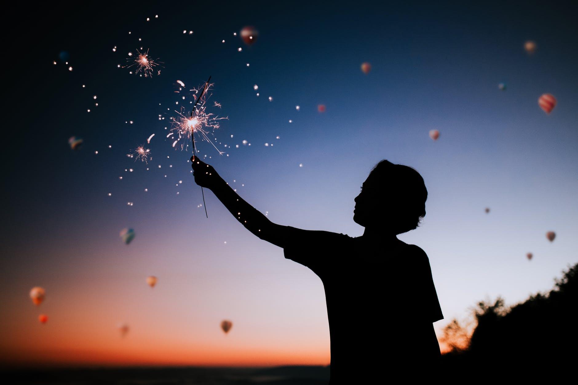 Silhueta de menino segurando um fogo de artifício aceso, a noite, com vários balões no céu ao fundo.