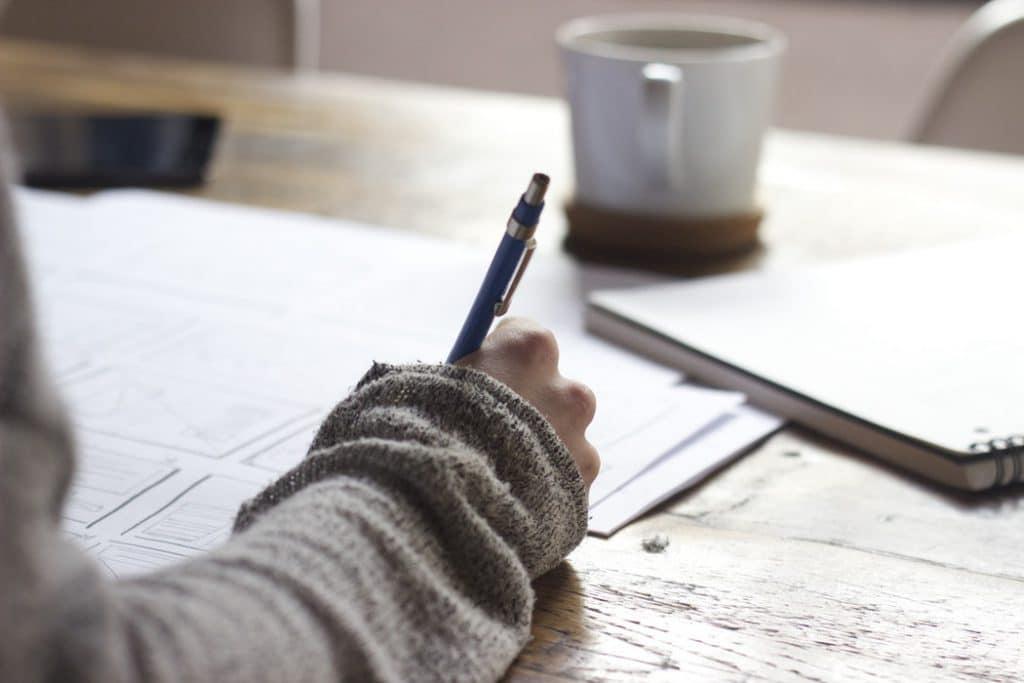 Imagem de uma pessoa escrevendo em um papel que está em cima de uma mesa.