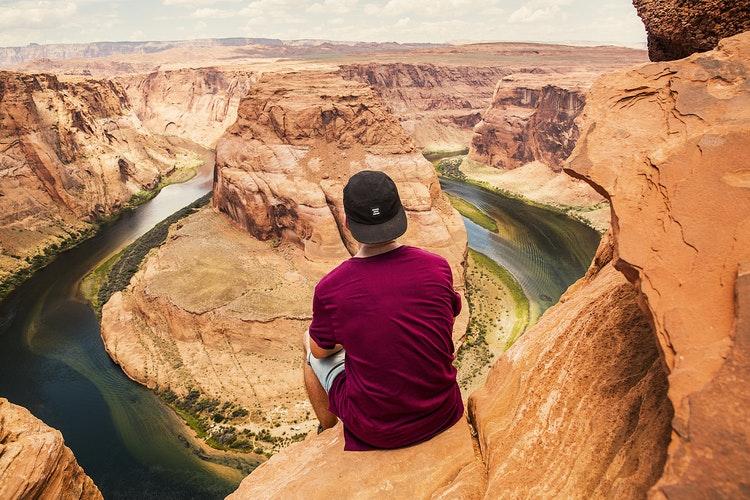 Homem sentado sobre uma montanha e ao fundo a paisagem é rochosa com um rio esverdeado passando entre as rochas marrons.