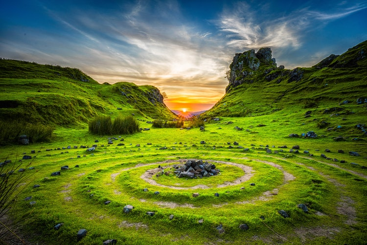 Foto de um grande campo aberto e verde. Ao fundo há o sol se pondo.