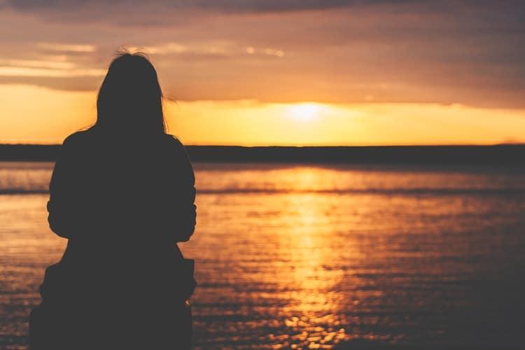 Silhueta de uma mulher observando o pôr do sol na praia.