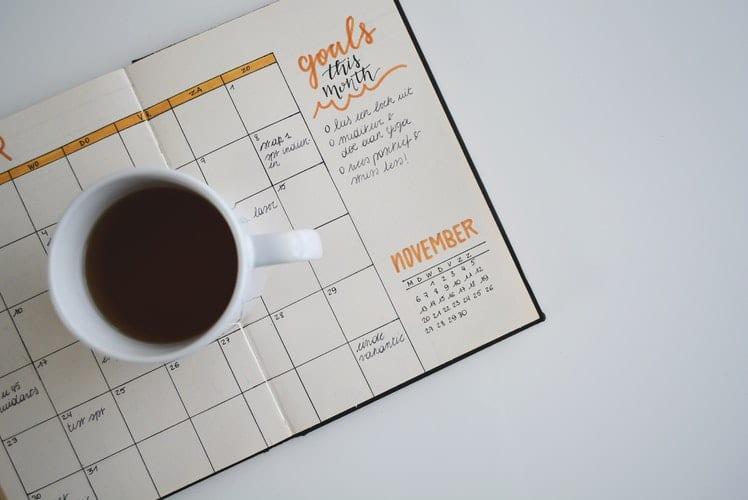 Agenda mensal com planejamento e listas de metas, em cima de uma mesa branca e com uma xícara de café.