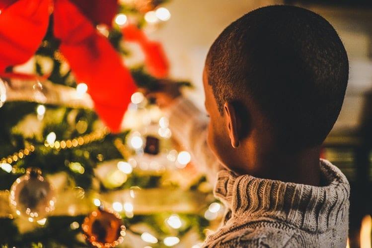 Menino em frente a uma árvore de natal toda enfeitada e iluminada.