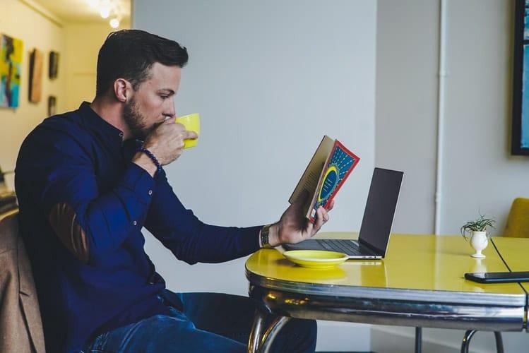 Homem sentado em uma mesa amarela. Ele está lendo um livro e ao mesmo tempo tomando algo em uma xícara amarela.