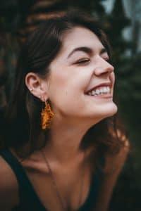 Mulher sorrindo de olhos fechados e ao fundo a paisagem são árvores.