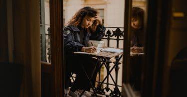 Mulher sentada em uma mesinha escrevendo em um caderno.