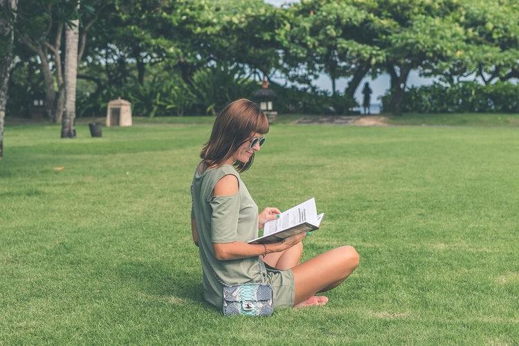 Mulher sentada na grama, em um parque, lendo um livro.