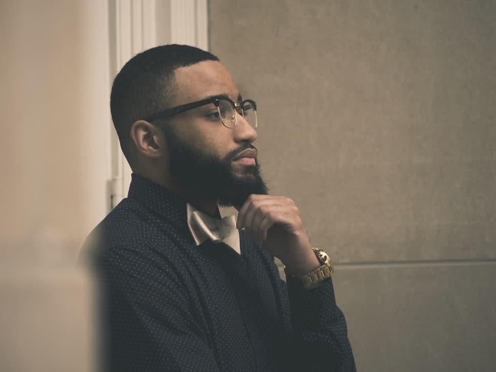 Homem em pose pensativa com a mão na barba.