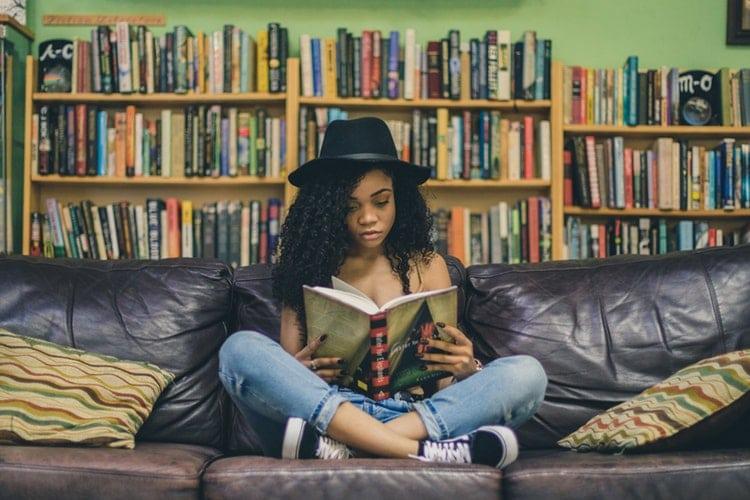 Mulher negra sentada em um sofá lendo um livro.