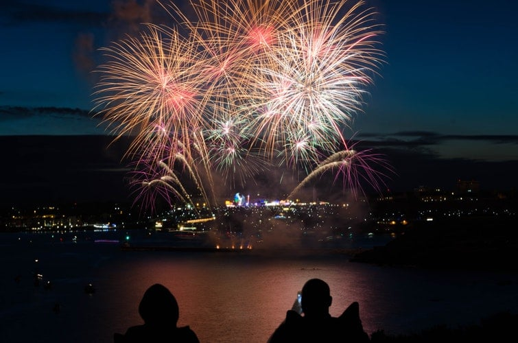 Pessoas observando a queima de fogos do ano novo.