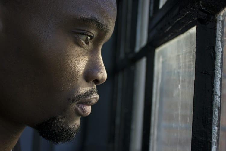 Homem olhando pela janela.