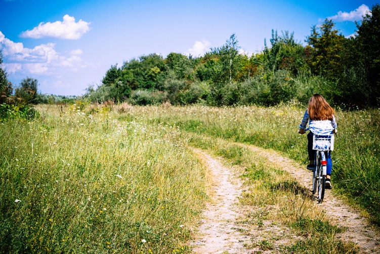 Mulher andando de bicicleta em um campo verde.