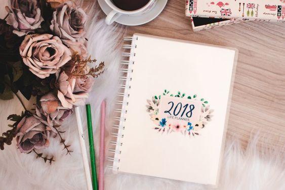 Agenda 2018. Canetas espalhadas, um vazo de rosas e uma xícada de café ao lado do caderno.