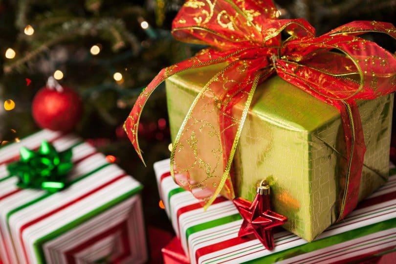 Presentes embrulhados, empilhados ao pé de uma árvore de natal decorada.