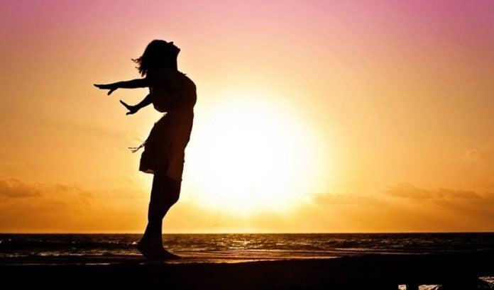 Silhueta de mulher se espreguiçando, em pé, próximo ao mar, com põr do sol ao fundo.
