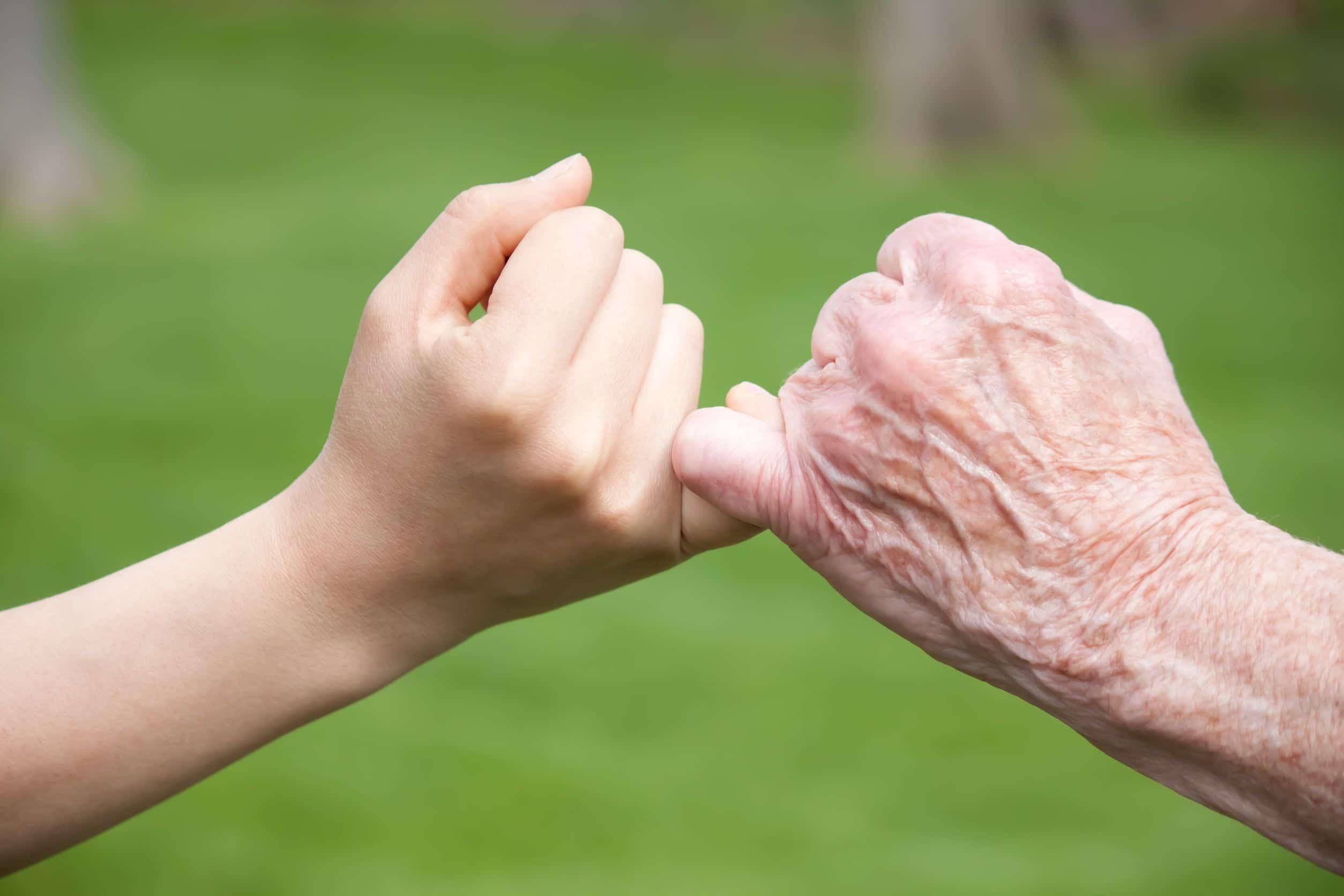 Mão de um jovem e um idoso dando os mindinhos em sinal de fazer uma promessa.