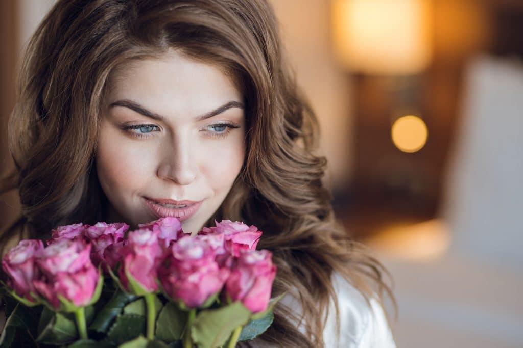 Mulher cheira buque de rosas.