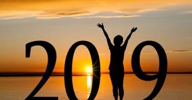 A silhueta 2019 do ano novo de uma menina com mãos levantadas, ocupando o lugar do 1 , na praia durante o nascer do sol dourado.