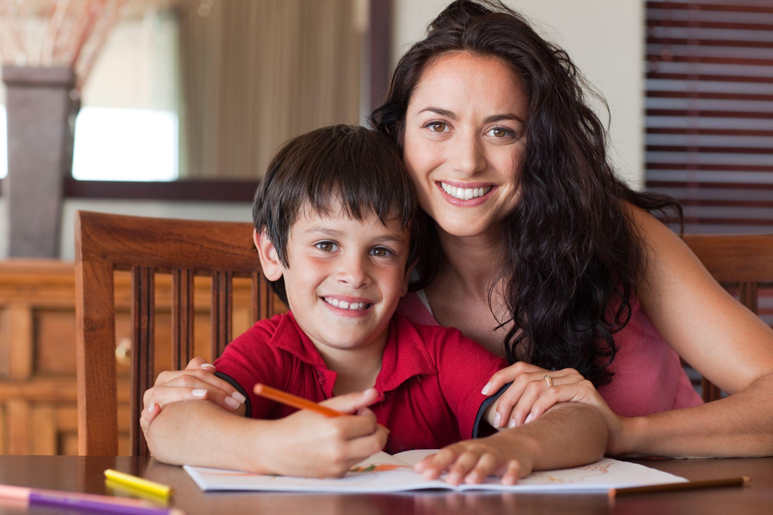 Mãe e filho felizes fazendo lição.