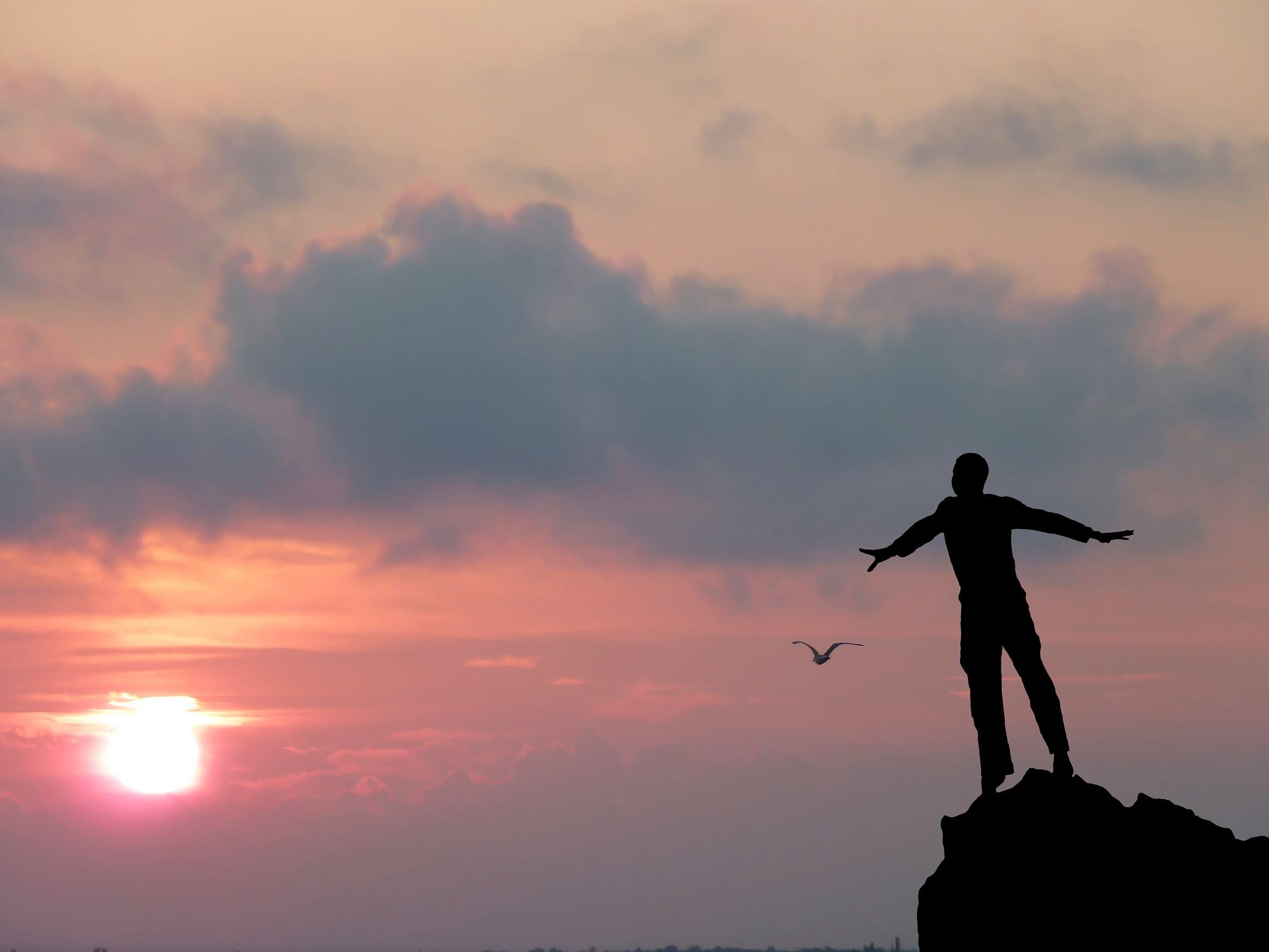 silhueta de um homem no topo da montanha olhando o céu