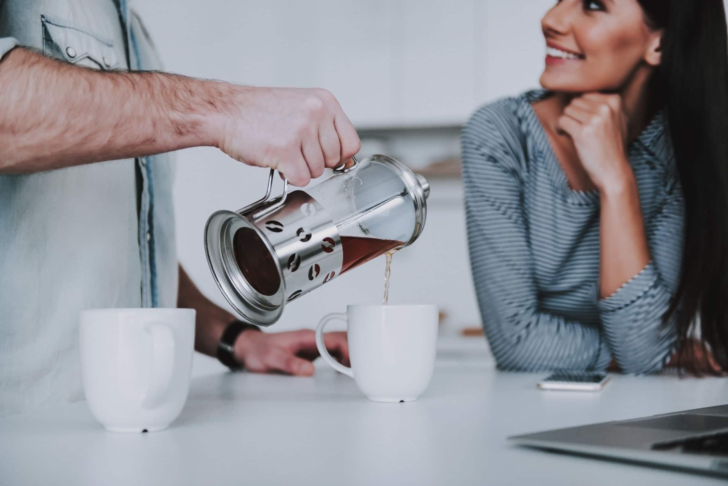 Homem despejando café em uma xícara enquanto uma mulher sorridente o observa.