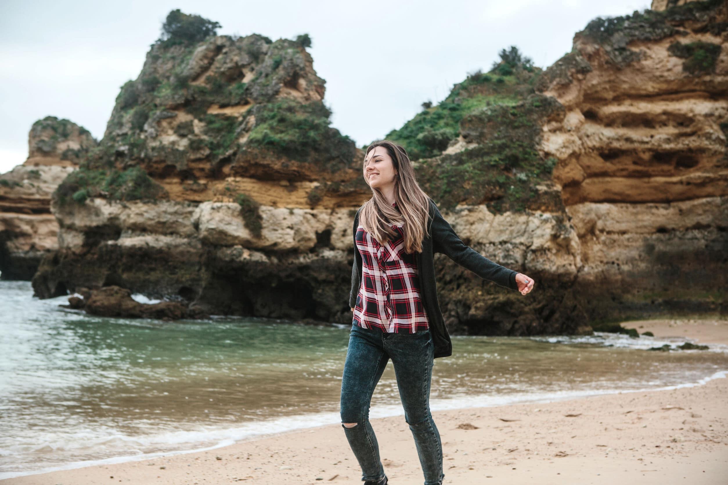 Menina branca correndo de braços abertos sorridente pela praia