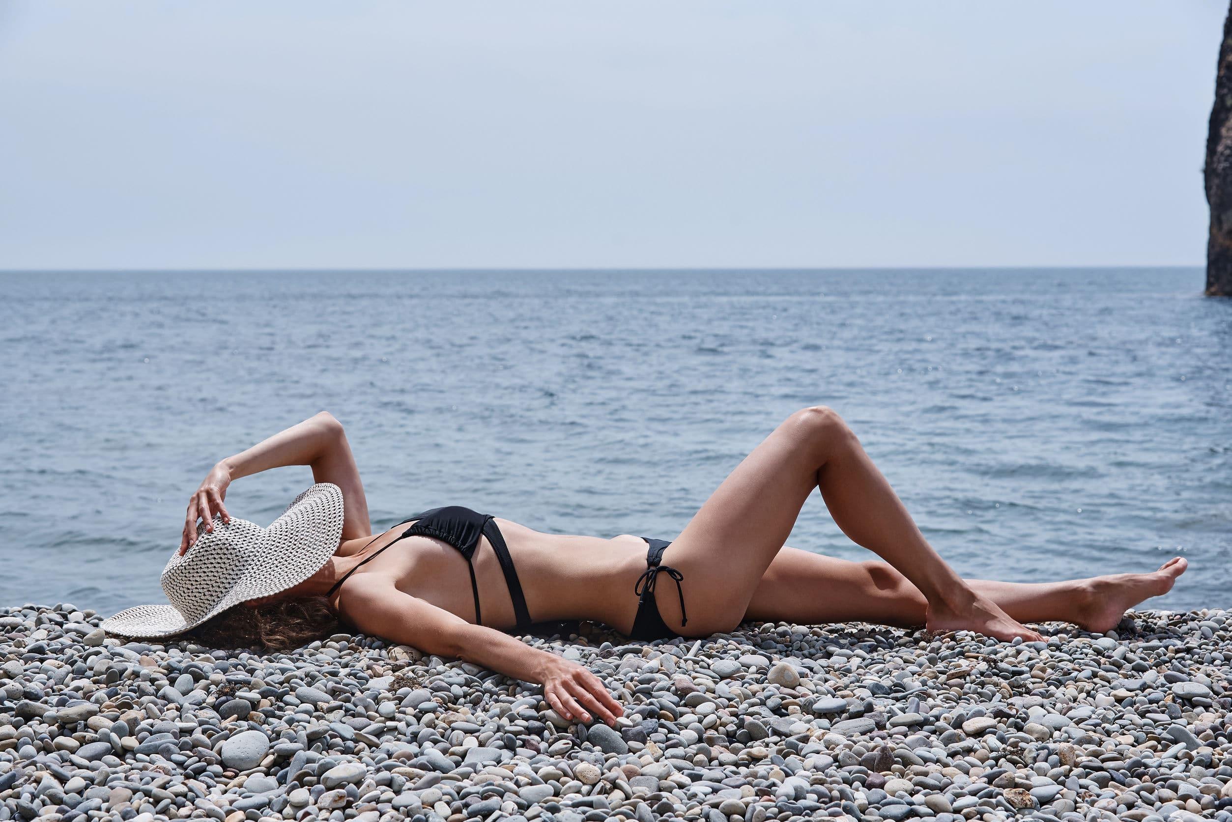 Mulher deitada em pedras na beira do mar com chapéu de palha cobrindo seu rosto enquanto toma sol.