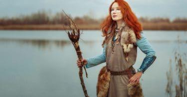 Mulher xama, em vestes de ritual, segurando um cetro de madeira.