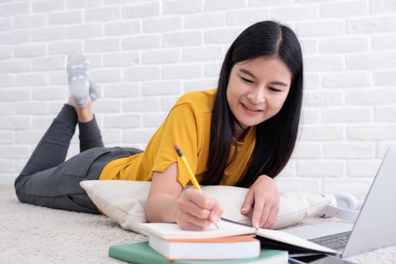 Adolescente asiática deitada na cama enquanto faz anotações em um caderno em frente ao computador.