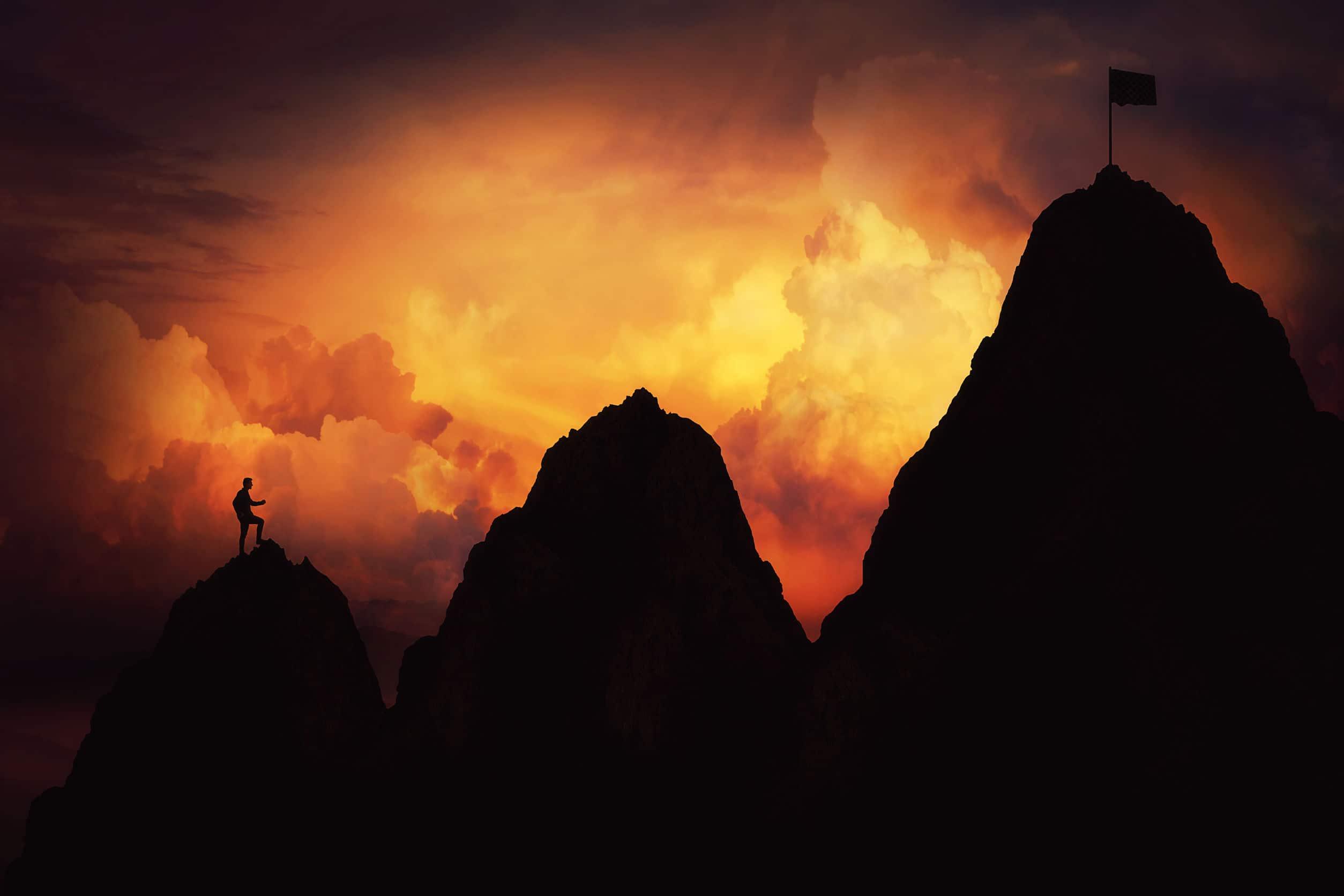 Silhueta de pessoa andando em montanhas, escalando em direção a uma bandeira que marca a chegada no topo.
