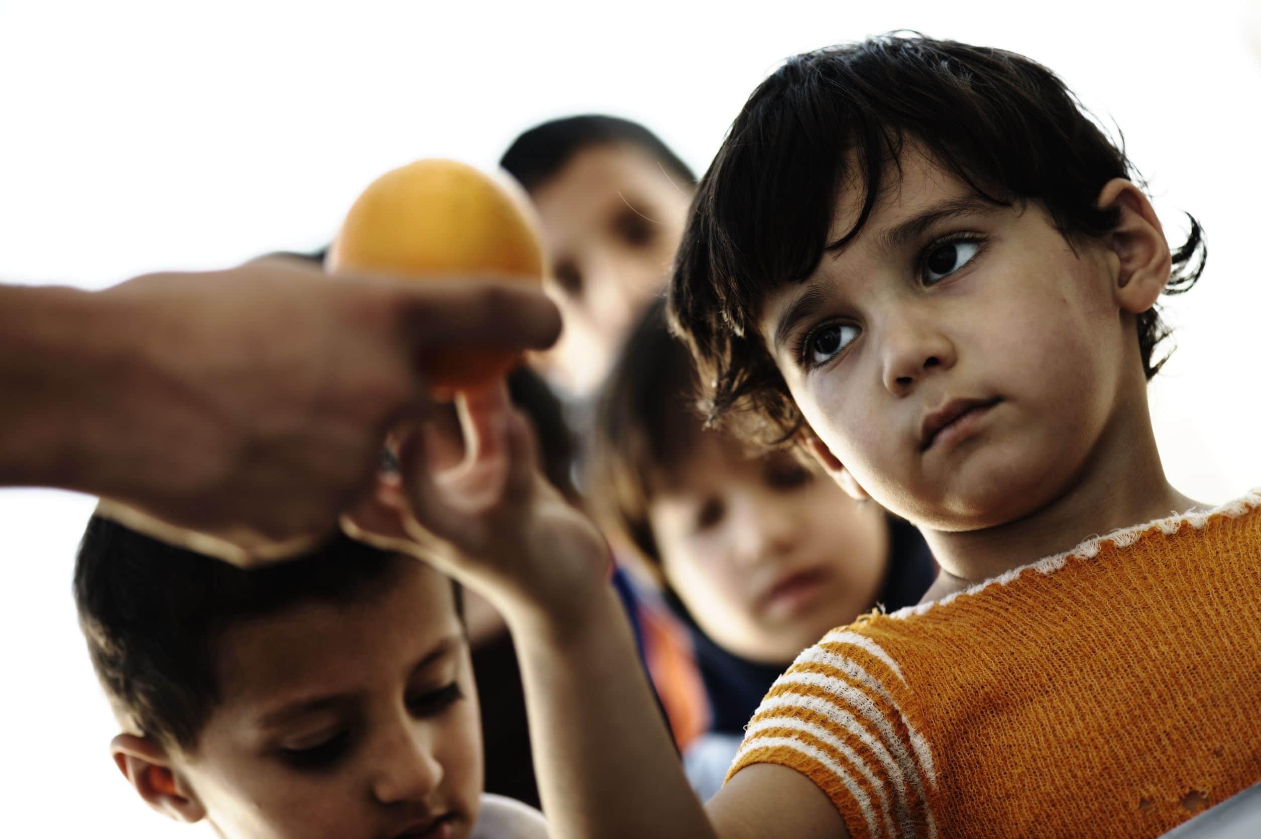 Fila de crianças carentes tristes e cabisbaixas, com a primeira criança da fila recebendo uma laranja da mão de um adulto.