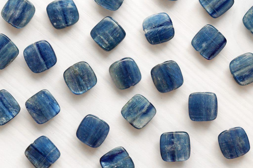 Pedras azuis de formato quadrado estão espalhadas em fundo branco. A pedra é chamada de Cianita Azul.