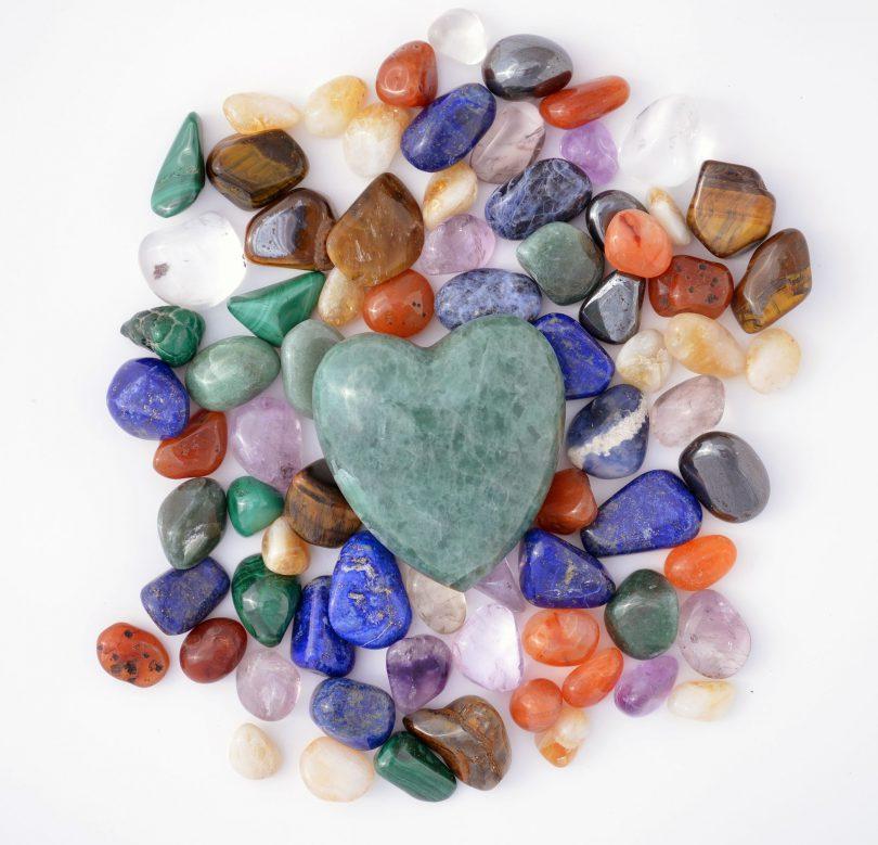 Coração de quartzo verde cercado de pedras coloridas diversas.