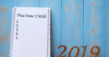 Caderno com planos para 2019. Fundo de madeira azul.