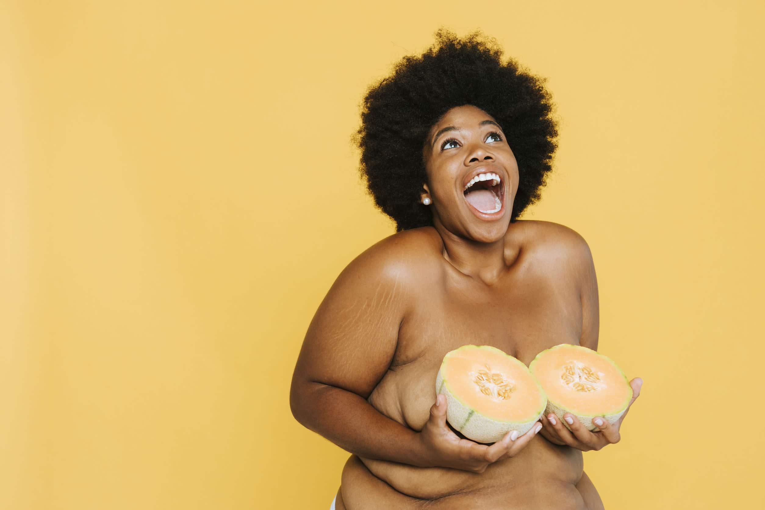 Mulher afro-americana curvilínea segurando melões no lugar dos seios