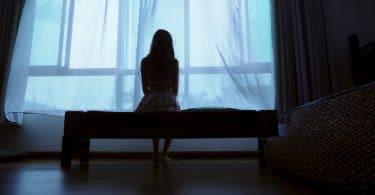 Menina sentada em uma cama olhando pela janela.