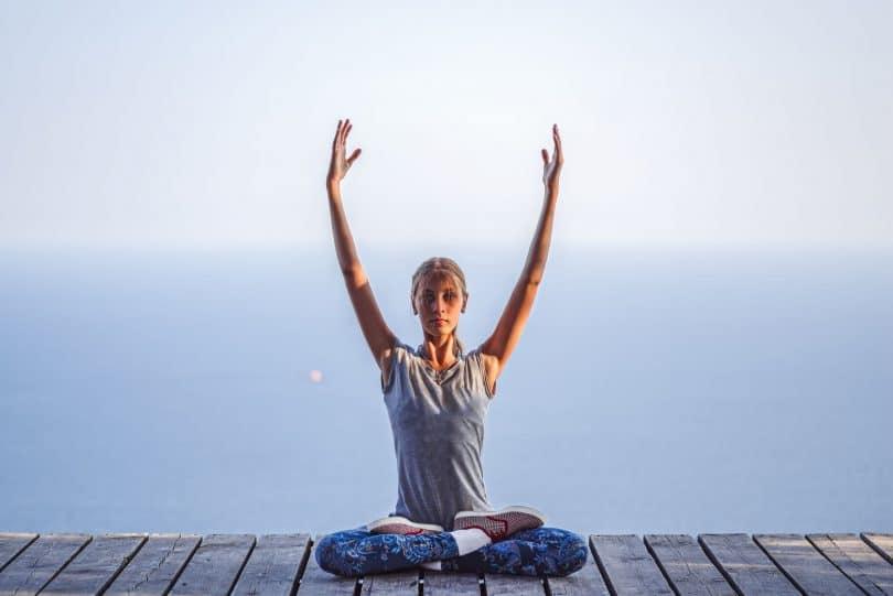 Menina em posição de lotus fazendo yoga.