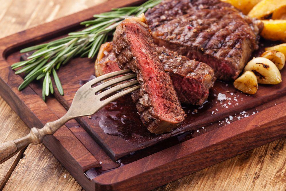 Carne vermelha com sal grosso, batatas ao lado e erva verde. Táboa de madeira usada como prato e garfo espetado em um pedaço de carne.