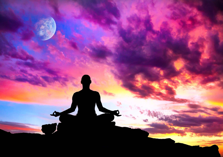 Silhueta de pessoa sentada em posição de flor de lótus meditando em cima de pedra com céu roxo ao fundo.