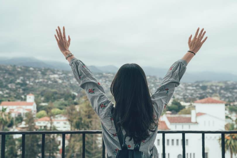 Mulher de costas com as mãos para cima.
