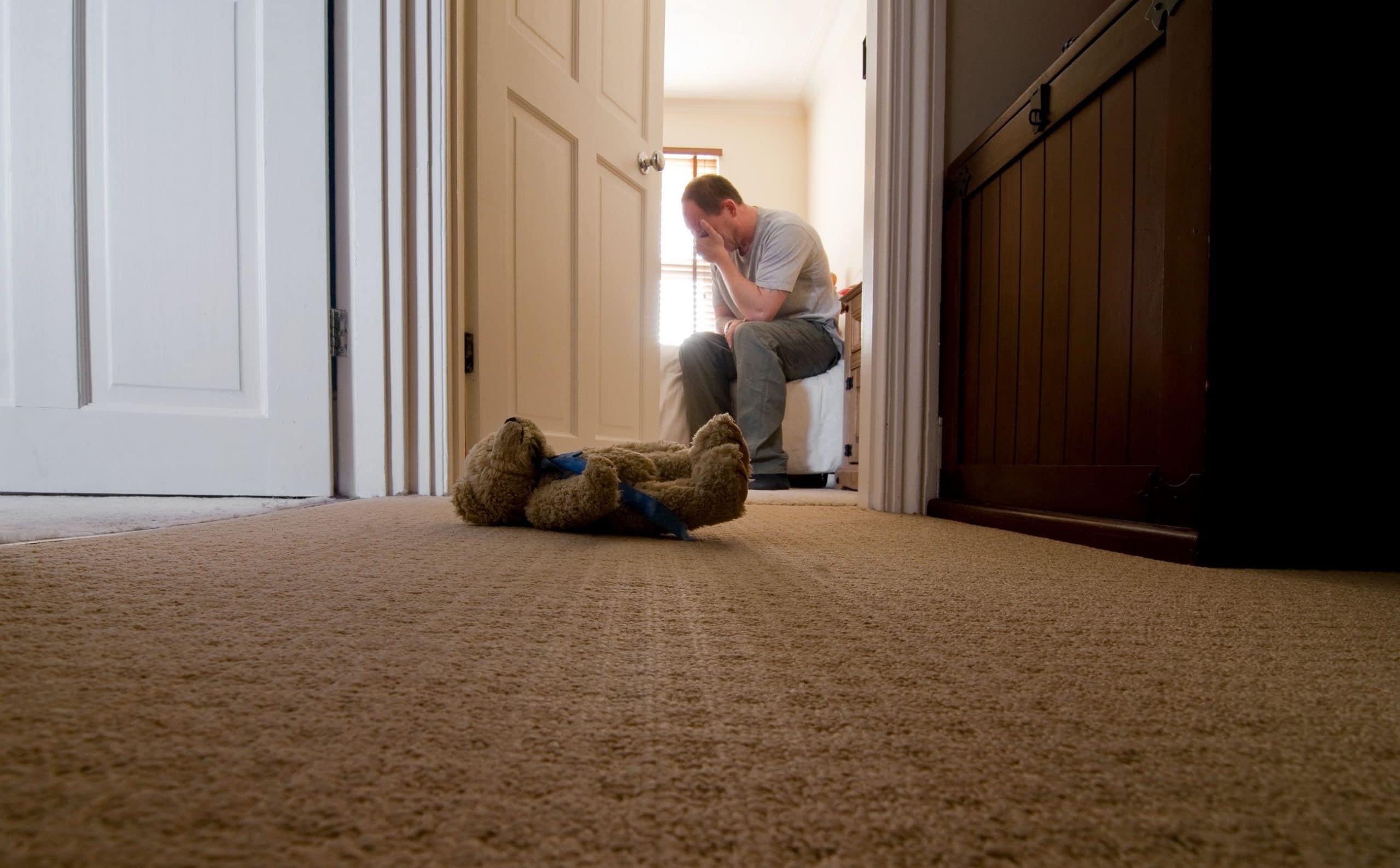 pai lamentando a perda de seu filho sentado na ponta de um cama, com um urso de pelúcia caído no chão do corredor.