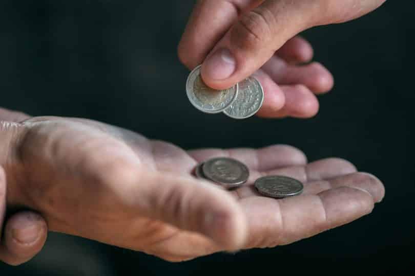 Pessoa entrega moedas à outra, que está com a palma da mão aberta.