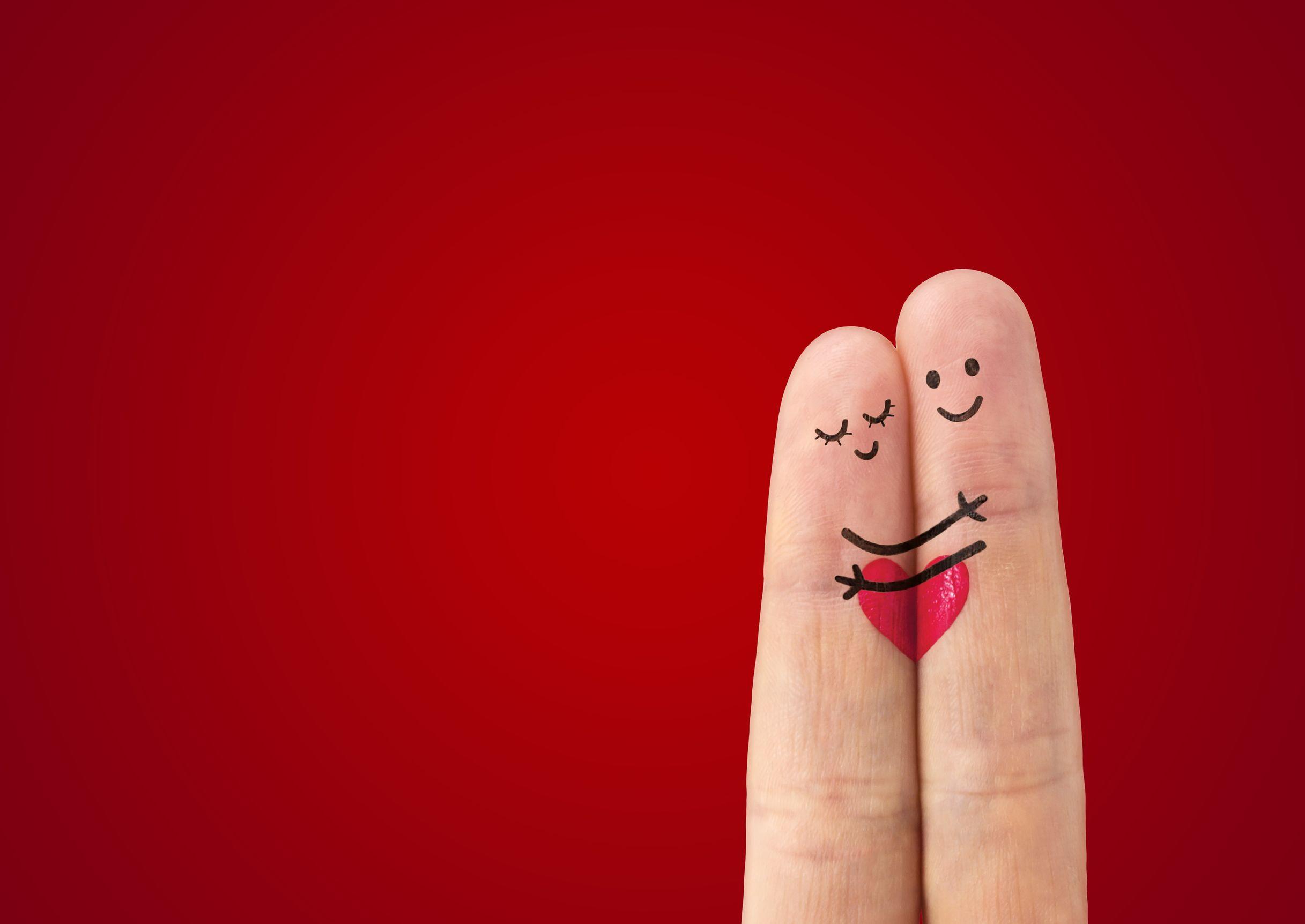 Desenho de casal abraçado feito em dois dedos de uma mão juntos com um fundo vermelho.