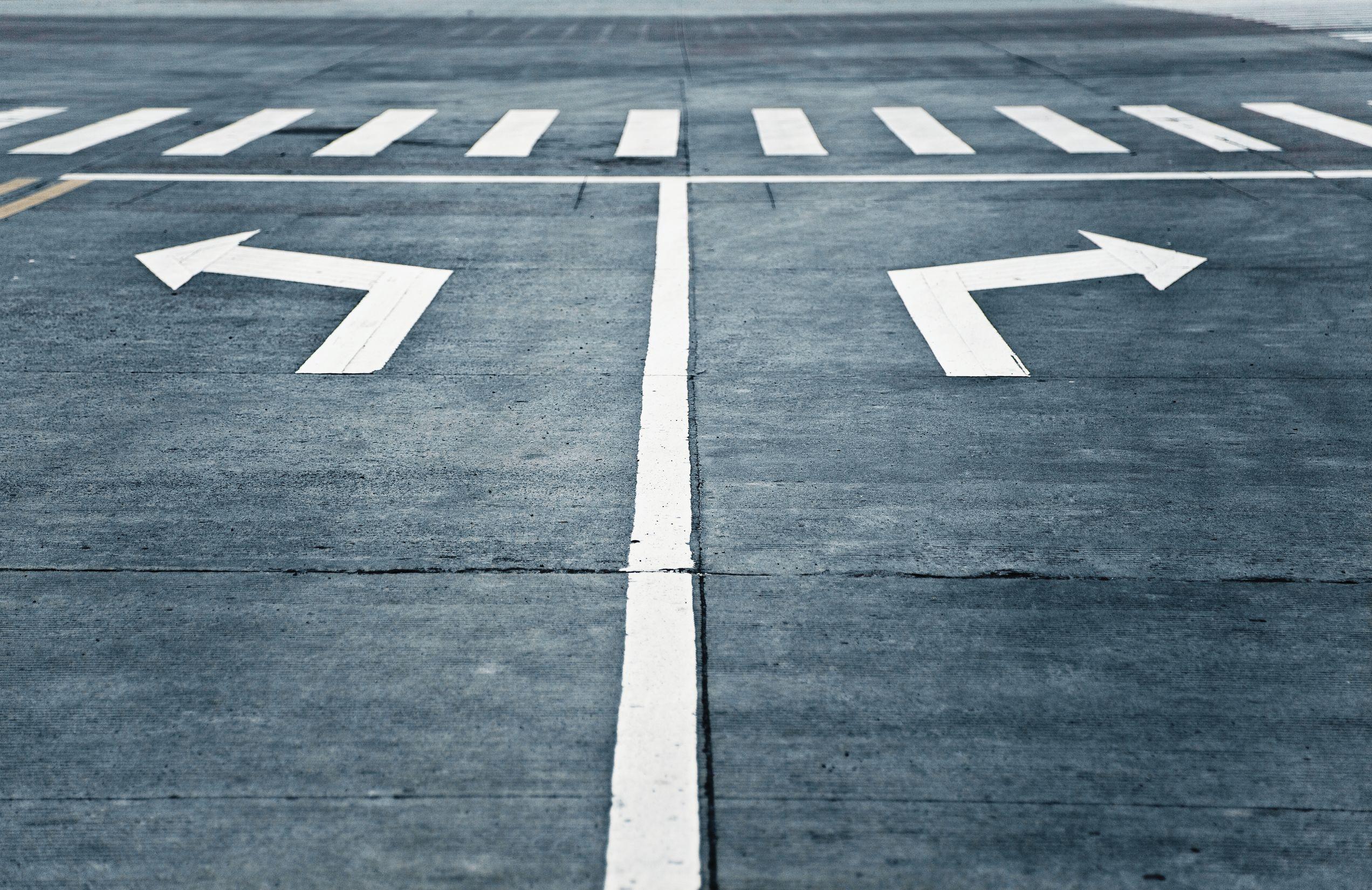 Sinalizações de estrada indicando curva para direita e curva para esquerda, ambas antes de uma faixa de pedestres.