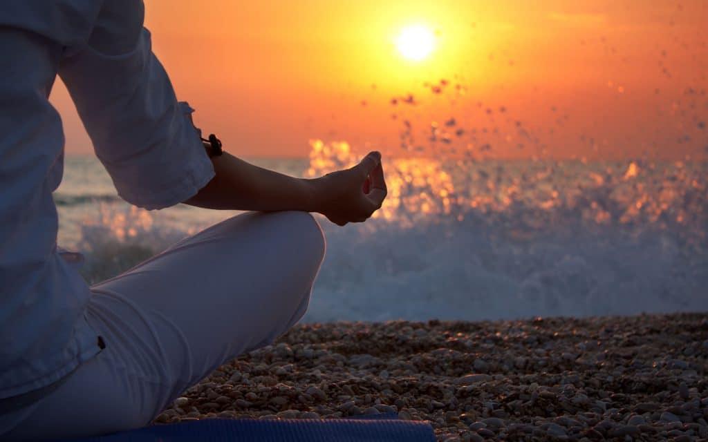 Mulher em posição mediativa na praia.