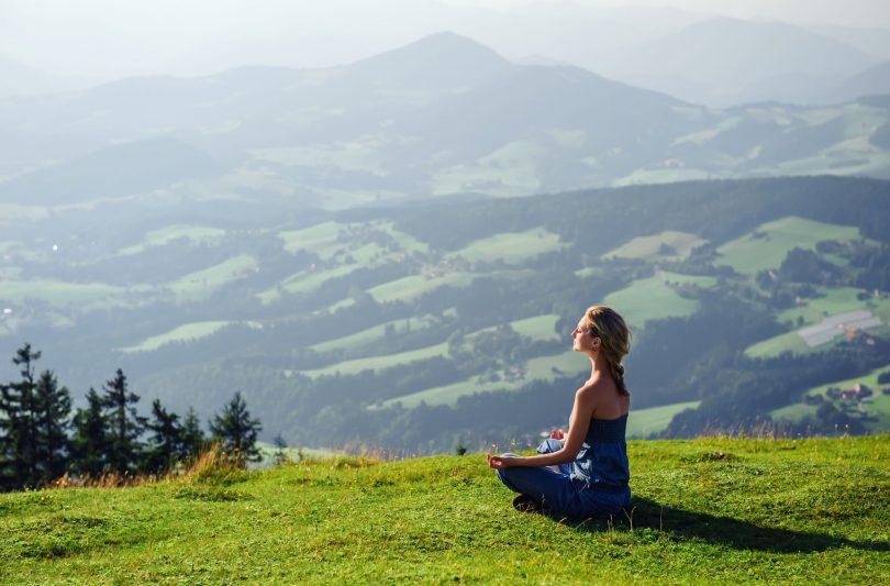 Mulher jovem sentada de pernas cruzadas meditando no campo.