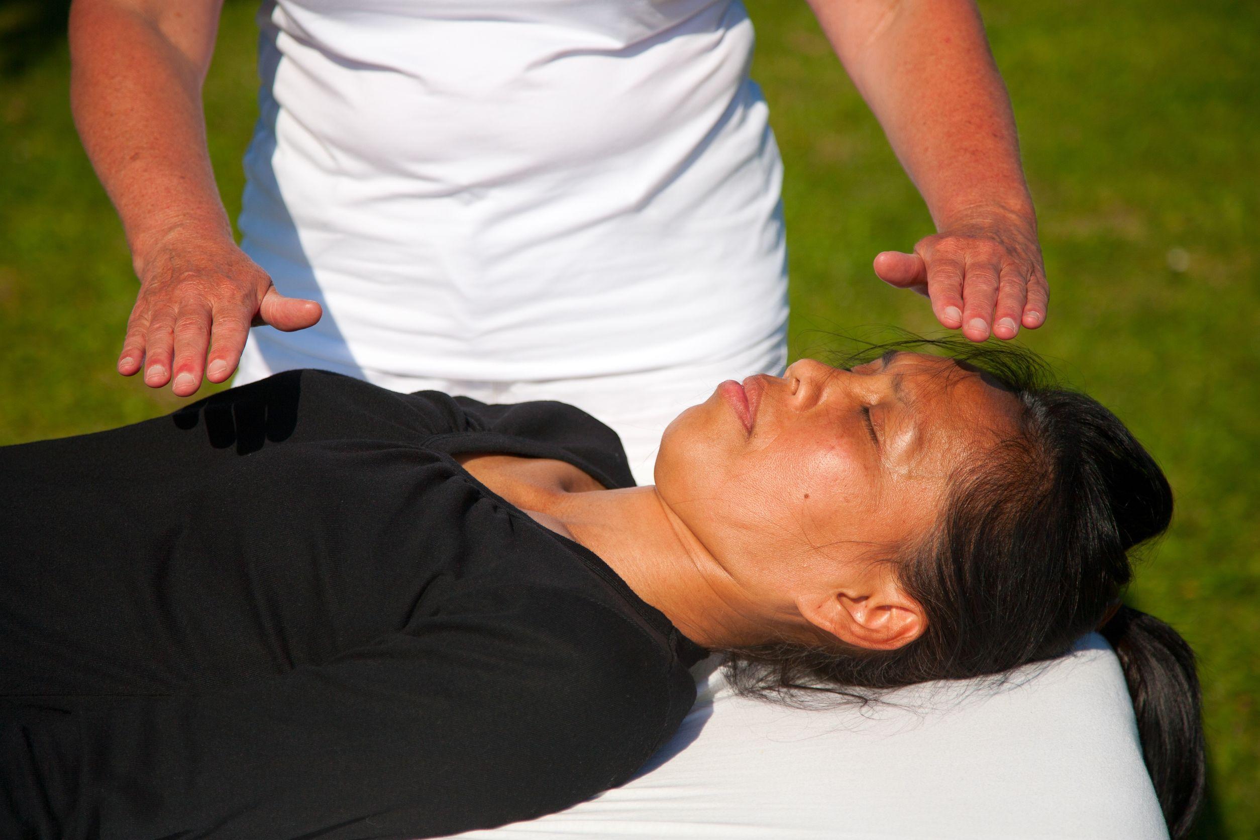 Mulher com descendência indígena deitada com os olhos fechados em uma maca recebendo uma massagem energética.