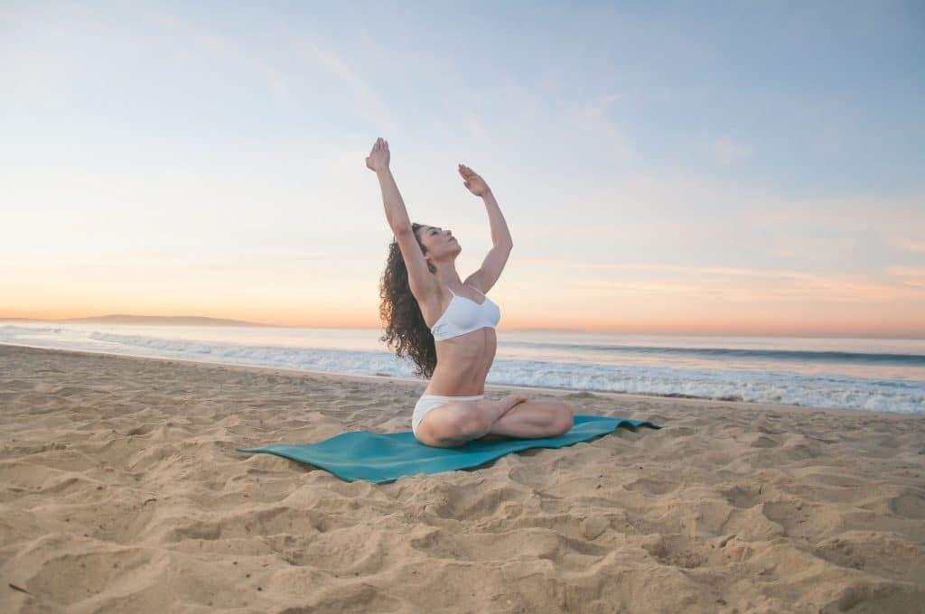 Mulher meditando em uma praia com as mãos para cima.